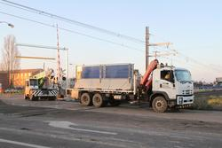 Construction equipment crosses the Aviation Road level crossing