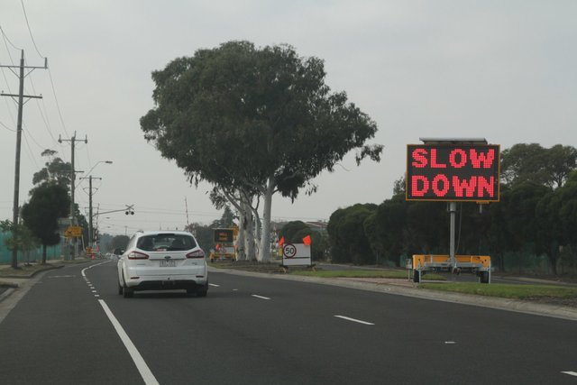 'Slow down' message for eastbound motorists approaching the temporary work site pedestrian crossing