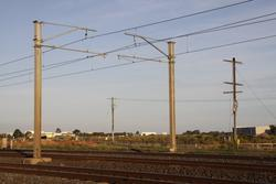 Lowered overhead wiring and power lines placed underground, a single mast from the old poleline still in place