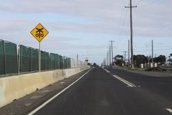 Grade separating Kororoit Creek Road on the Geelong line: Looking west towards the level crossing, worksite fenced off