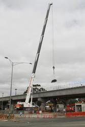 Werribee Street level crossing removal project: Crane lifting scaffolding to the top of the bridge deck