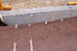 Metal straps hold the concrete retaining wall panels in place