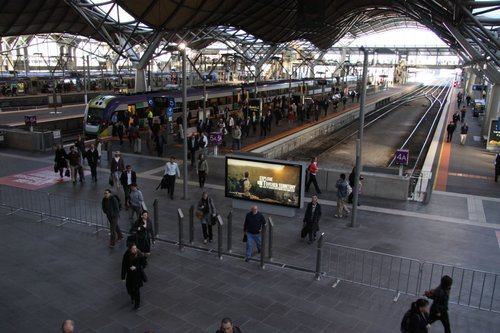 Passengers stream off the train and squeeze through the narrow gap for the future Myki ticket barriers