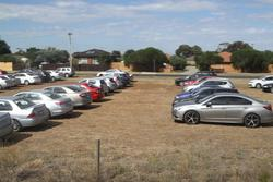 Ad hoc dirt car park on the south side of Melton station full of cars