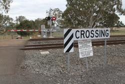 'Obtain permission from train control before transferring livestock or heavy machinery' sign at an occupation crossing