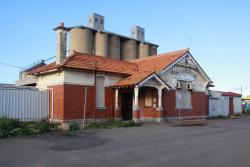 Borded up station building, the silos behind