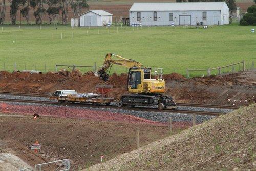 Hi-rail excavator rolling along the tracks towards Tarneit at Dohertys Road