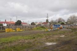Temporary fencing and crash barriers stored on the cleared land on Buckley Street