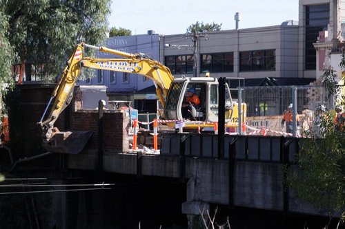 Excavator hanging it's bucket over the edge of the bridge to catch debris