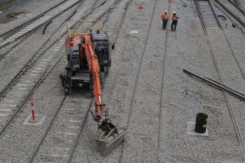 Hi-rail excavator tweaking freshly laid ballast