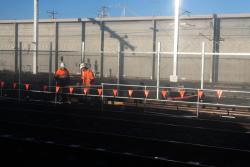Workers installing a fence between the RRL tracks and the Through Goods Line
