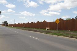 Steel noise walls line the railway parallel to Forrest Street