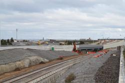 Tracks transition from embankment to cutting at Lollypop Creek, with the new Armstrong Road extension taking shape to the east