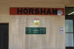 Horsham: V/Line orange station sign above a modern The Overland timetable